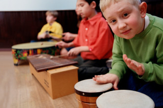 Group of students (8-10) playing musical instruments in classroom
